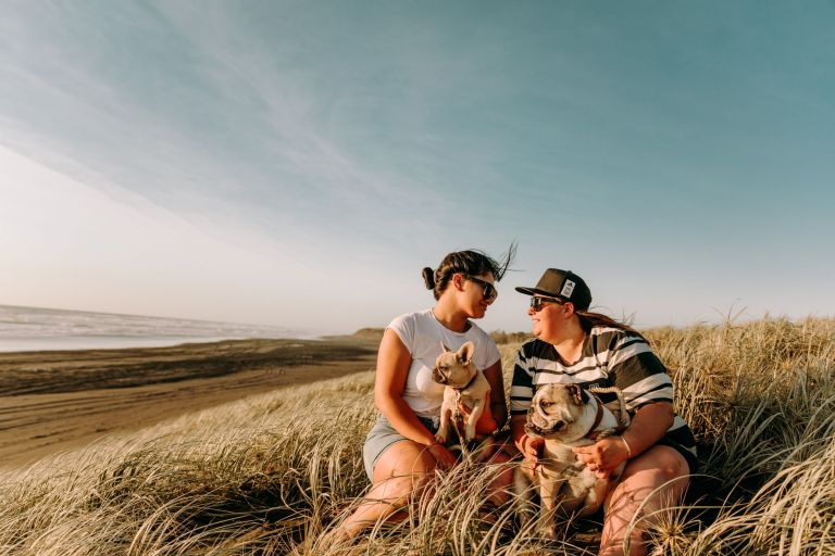 Same sex couple's engagement shoot sitting at Muriwai Beach with dogs