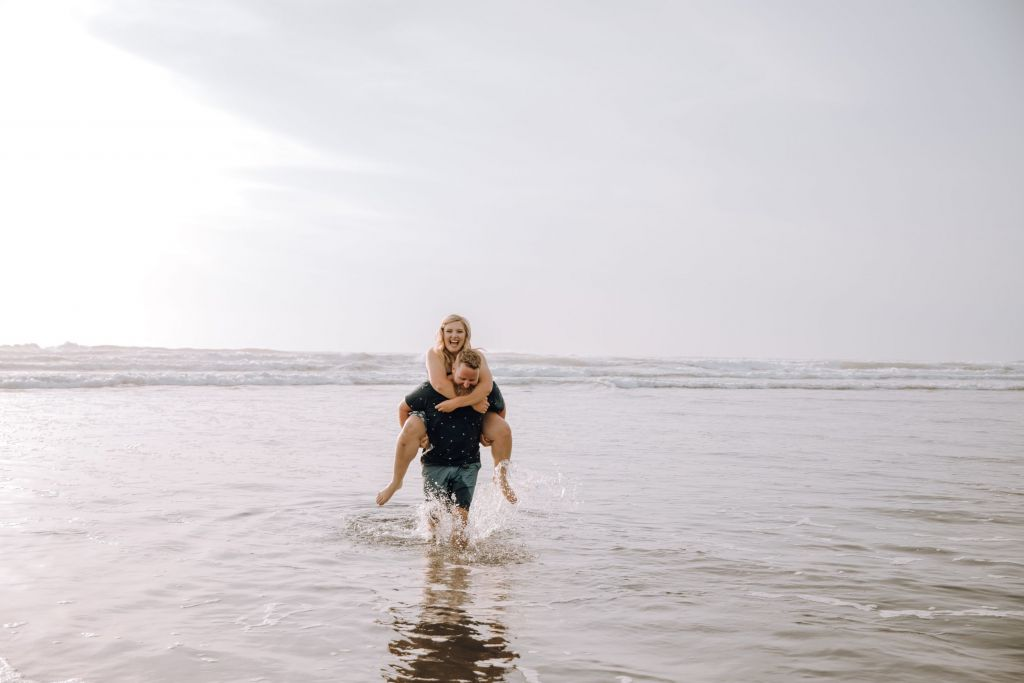 Piggyback Couple at Beach Engagement Session Piha Beach